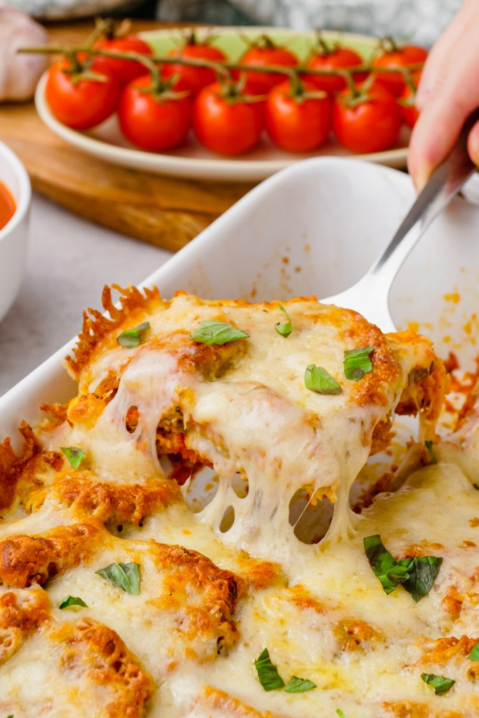 Eggplant parmesan in a white baking dish, being scooped out by a metal spatula, tomatoes in background