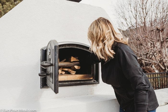 Putting wood in a wood fired oven to start it.