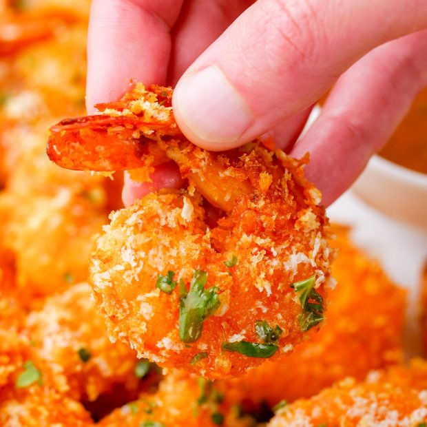 A hand holding a crispy oven baked shrimp, tail on