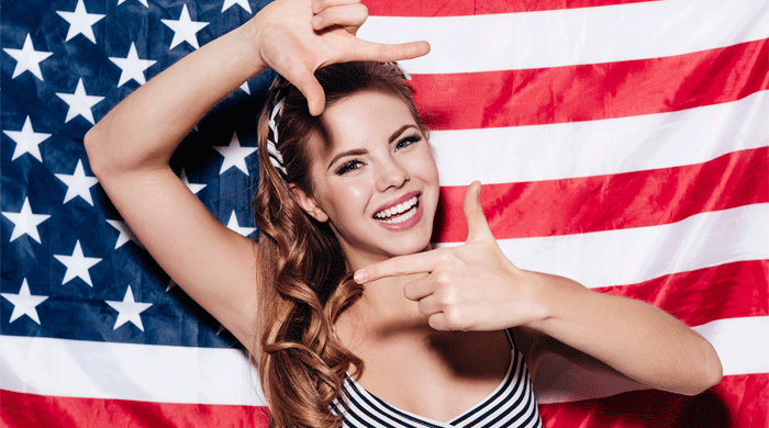 woman smiling in front of an american flag