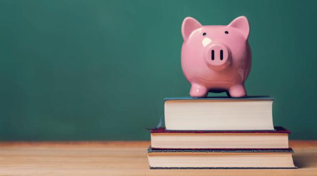 Piggy bank on top of school textbooks