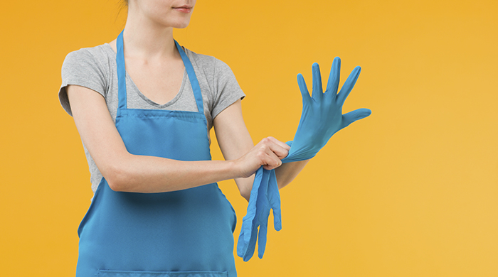 Woman Putting on Blue Kitchen Gloves