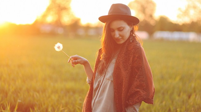 Girl wearing hat in a field holding a dandelion