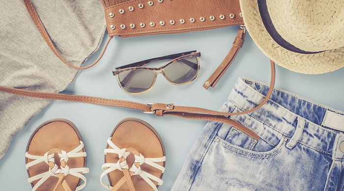 Spring fashion outfit lay flat overhead shot on blue background