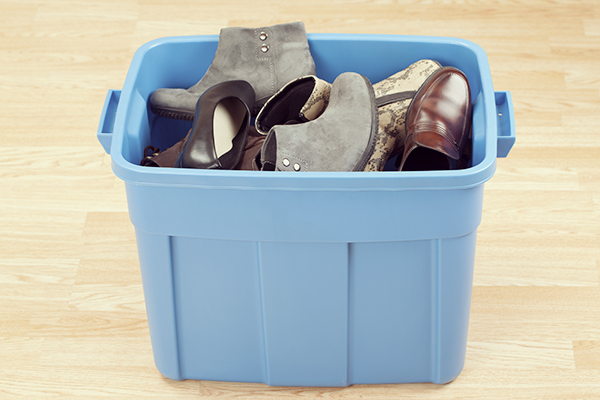 Plastic storage box filled with a variety of shoes on a hardwood floor.