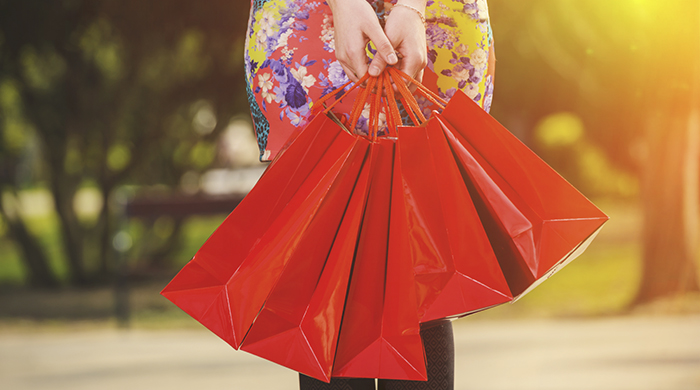 Woman in floral dress holding red shopping bags