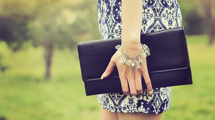 Girl wearing charm bracelet holding black clutch