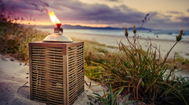 Citronella candle bug lantern on the beach at sunset