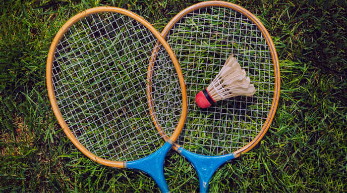 Badminton rackets and birdie on grass