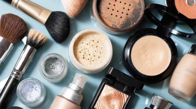 Overhead shot of makeup and brushes on blue background