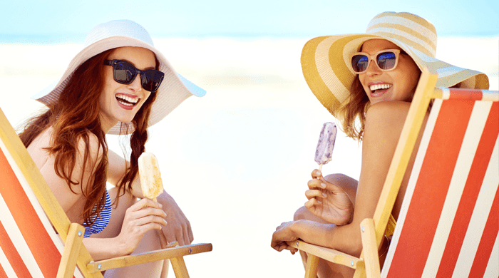 Two women on the beach eating popsicles