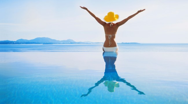 Woman standing in the ocean with arms raised summer vacation