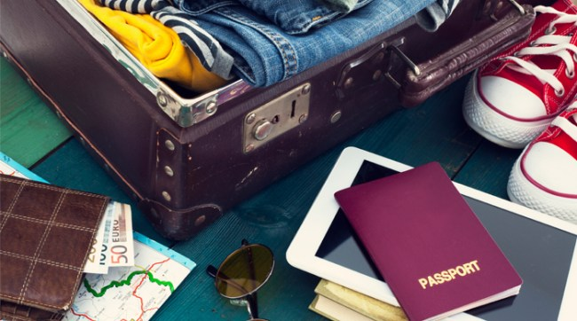 Packed suitcase with map, passport, sunglasses and tablet