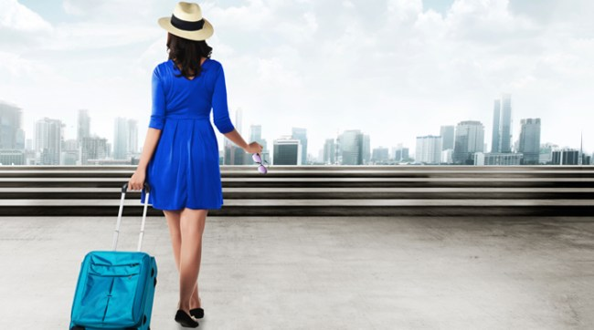 Woman in blue dress walking with rolling suitcase