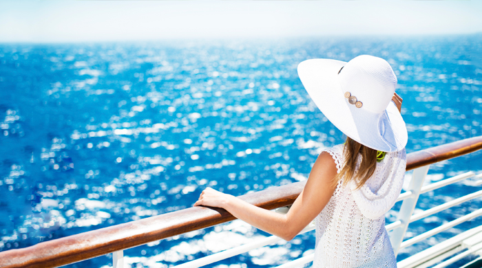Woman in white hat standing on the deck of a cruise ship