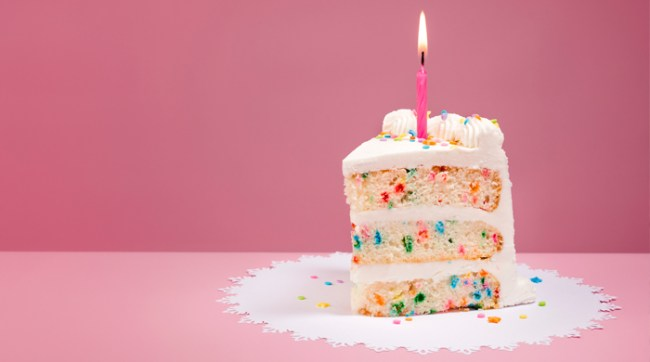 White birthday cake with candle on pink background
