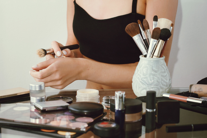 Girl doing make up, pushes concealer on hand. Blurred cosmetics foreground. White background.