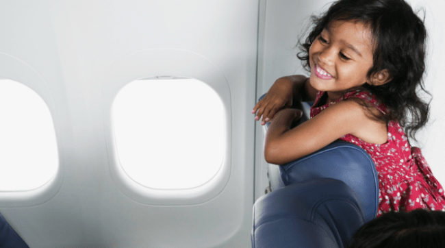Little girl looking over her seat in an airplane
