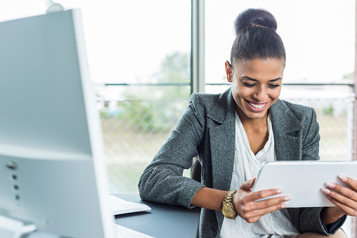 Smiling young woman in office looking on digital tablet
