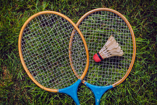 Vintage badminton rackets and shuttercock lying in grass