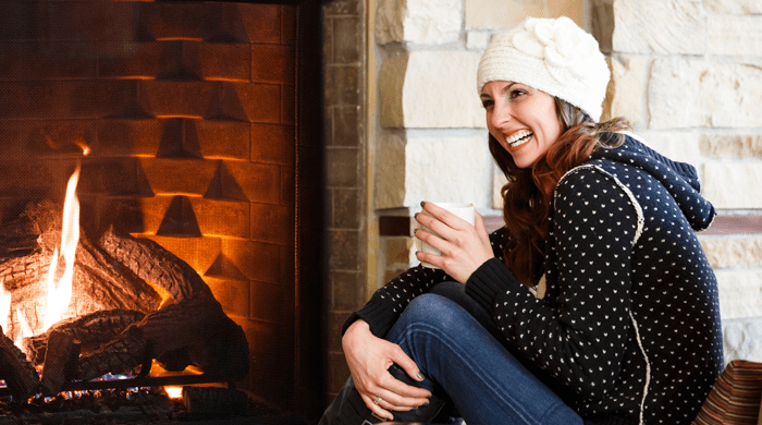 woman sitting by a fire in a fall sweater
