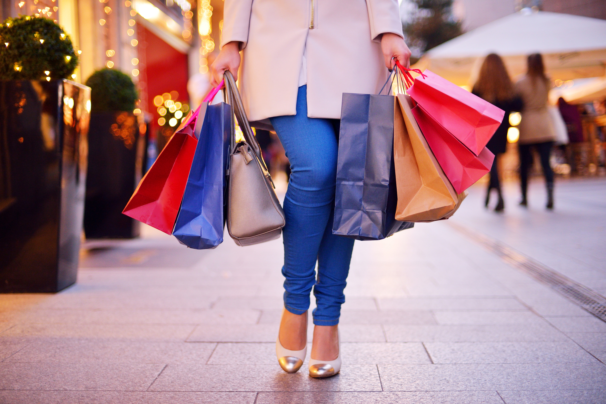Young woman shopping in the city, legs and hands close up, carrying paper bags.