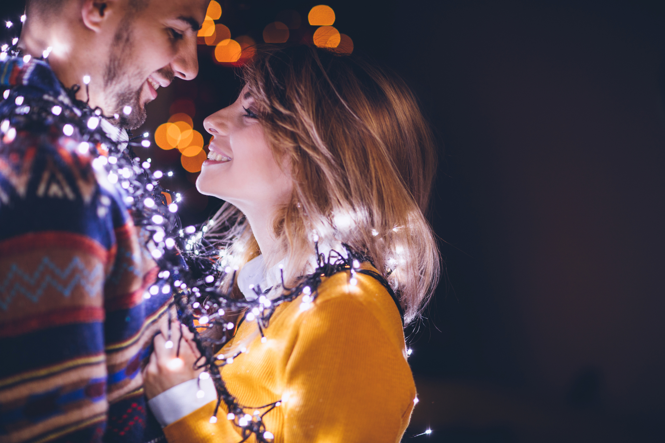 Couple embracing wrapped in Christmas lights