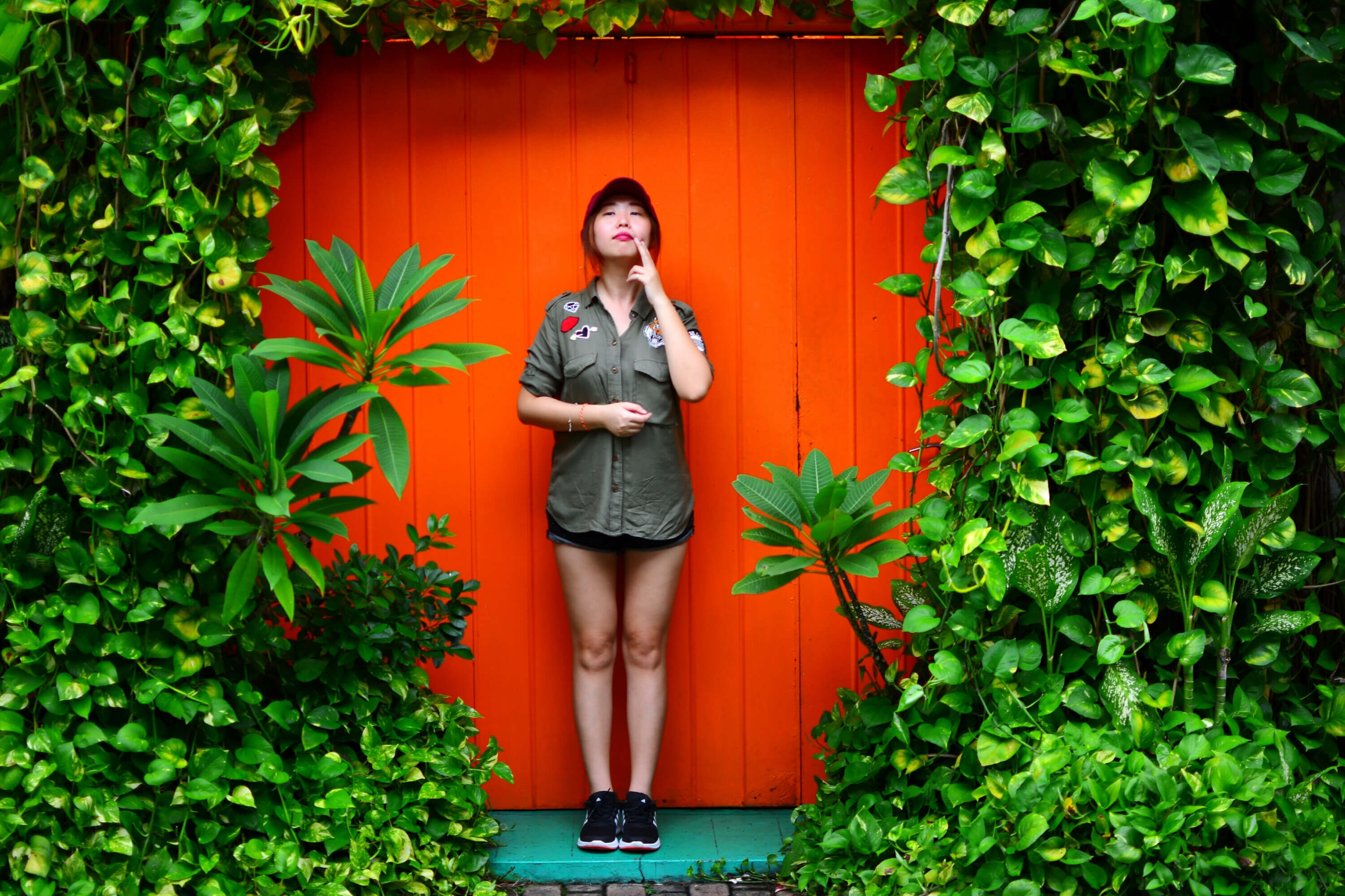 Girl Standing In Front of Red Door with Ivy