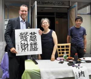 Greg Riley, general manager of Holiday Inn Manhattan-Financial District with calligraphers from the China Institute
