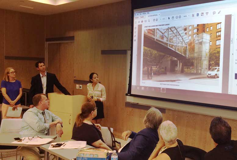 The Economic Development Corporation's Lynne Guey (left) and Julia Melzer (right), with Skanska engineer Matt Krenek (center), review plans for the West Thames pedestrian bridge, as members of  Community Board 1's Battery Park City Committee look on.