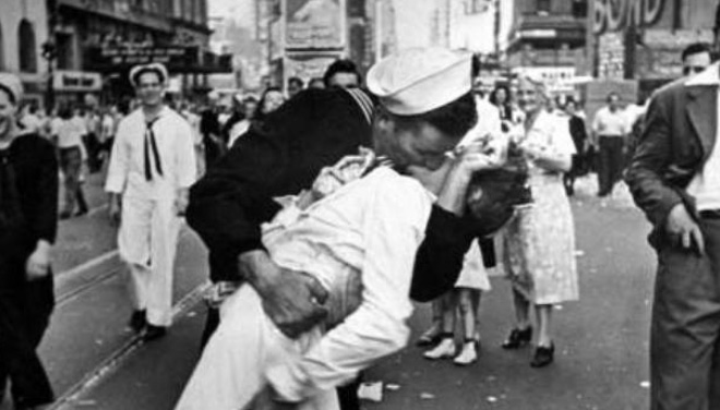 """V-J Day in Times Square is a photograph by Alfred Eisenstaedt that portrays a U.S. Navy sailor grabbing and kissing a stranger-a woman in a white dress-on Victory over Japan Day (""""V-J Day"""") in New York City's Times Square on August 14, 1945"""
