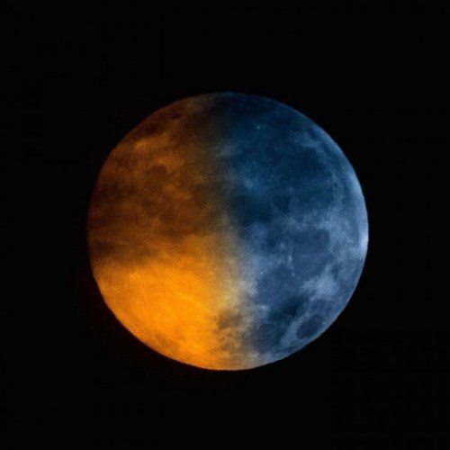 """Blue moons don't really look blue in color. Greg Hogan got this shot of the Blue Moon (blue in name only!) in a cloudy sky on July 31, 2015. He wrote: """"Having some fun with the blue moon idea... I blended the same image twice one with a blue tint, and one normal.  (courtesy EarthSky.org)"""