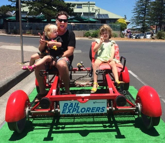 Byron Shire mayor Simon Richardson and his children pose for pictures in a Rail Explorers' 'rail bike' at Apex Park in Byron Bay. Photo Mary-Joy Lu