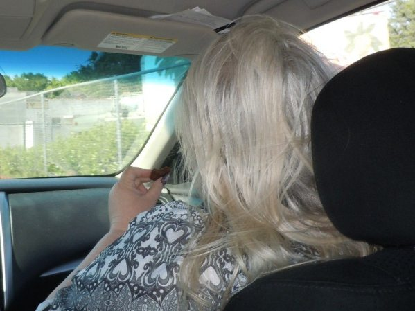Woman with grey blond hair in a car