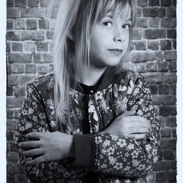 Portrait, portraiture, children's portraits, studio photoshoot, studio photography, walled back drop, walled back drop photography, de-saturated imagery, de-saturated portrait, young girl with attitude