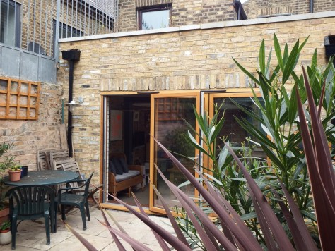 A side return extension featuring bricks reclaimed from demolition in the house, a green roof and triple glazed bi-fold doors.
