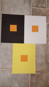 Contrasting three same size orange blocks on black, white and yellow sheets.