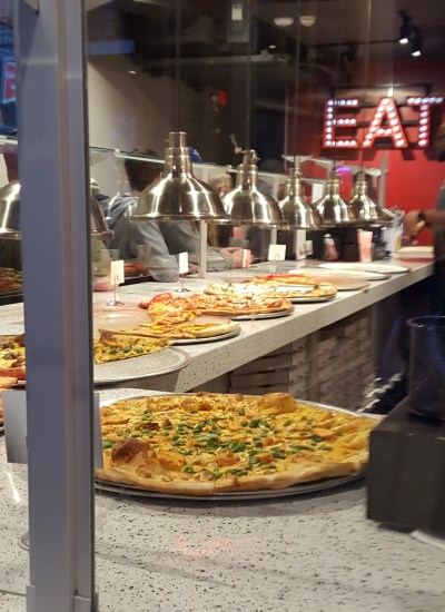 Pizzas lined up for sale by slice