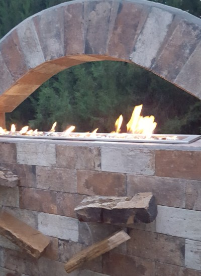 Fireplace with flame and waterfall with water on custom built feature