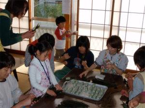 団子を笹で包んで、すげを巻きつけて結ぶ作業です。すっかり無口になってしまう参加者が続出しました。
