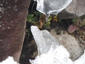 雪の壁の上の方の雪がとけて、その水が下の方にたまり、絶え間なくしずくが落ちていました。