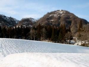 集落のシンボル・たる山と、雪の原になったふもとの田んぼ。雪の原の表面には筋状の模様ができていました。雪はとても表情が豊かです。