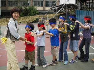 目隠しをし、イモムシのように連なって「冒険の旅」に出た参加者たち。左が井東敬子さん