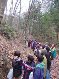 すっかり葉を落とした雑木林の中で、説明を聞く参加者のみなさん。