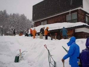 一階部分がすっぽり雪に埋もれた高齢者宅の回りで雪掘りをする参加者のみなさん。