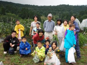 3日目、笛木和子さんの畑の前にて。たくさんの野菜を収穫させてもらいました。