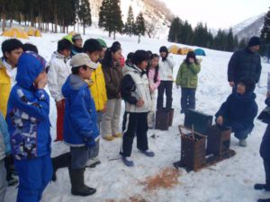 雪の上でのたき火は、一斗缶を使って起こします。後ろのテント群がお泊まりの場所となりました