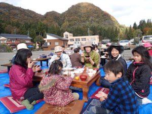 紅葉が鮮やかな樽山(736m)を背景に、地元の子どもたちも加わった収穫祭