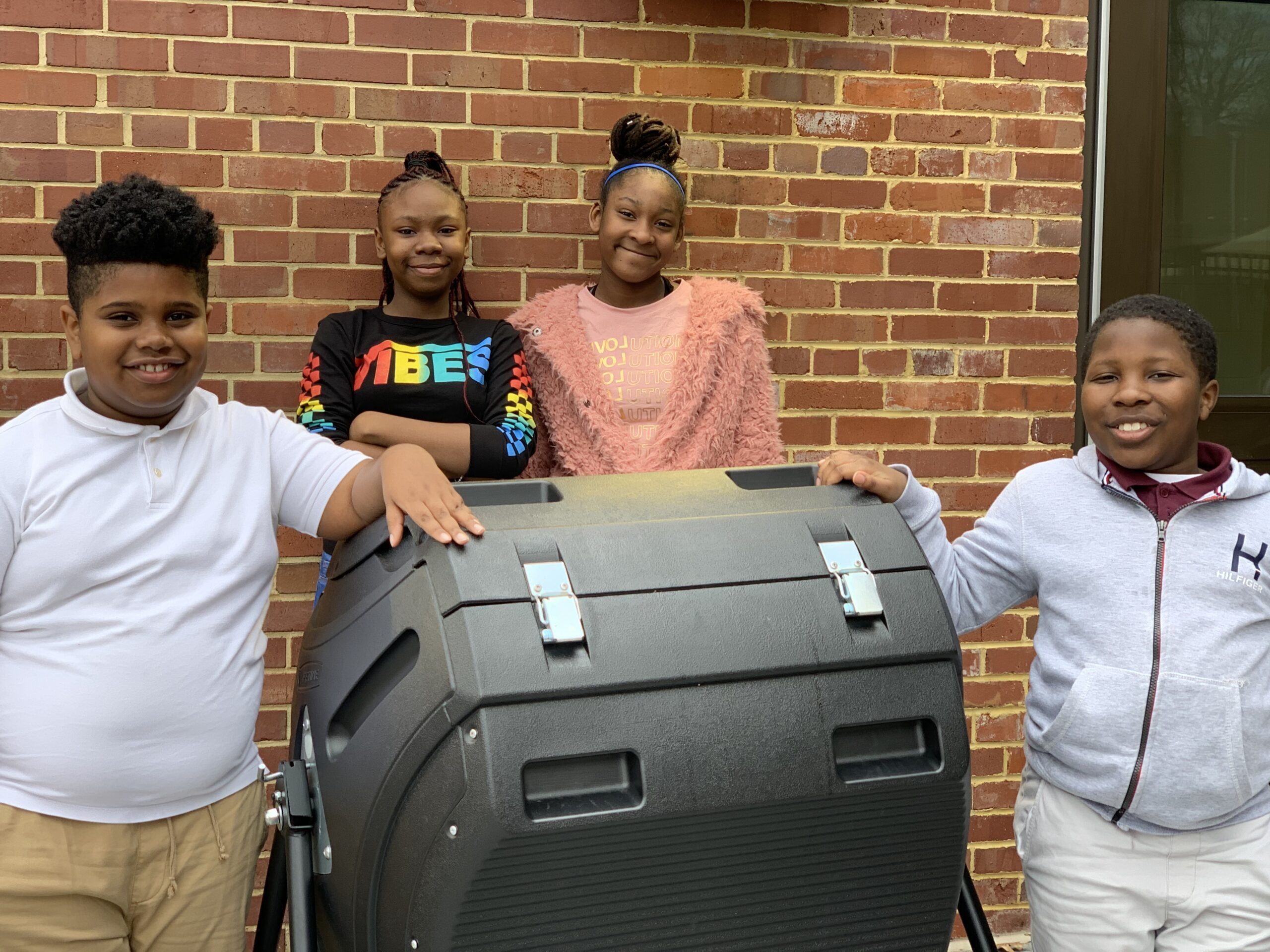 C W Harris Elementary students posing with their new compost tumbler bin