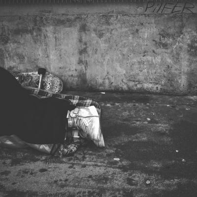 Photo of worn shoes of someone lying on dirty pavement, skateboard next to them